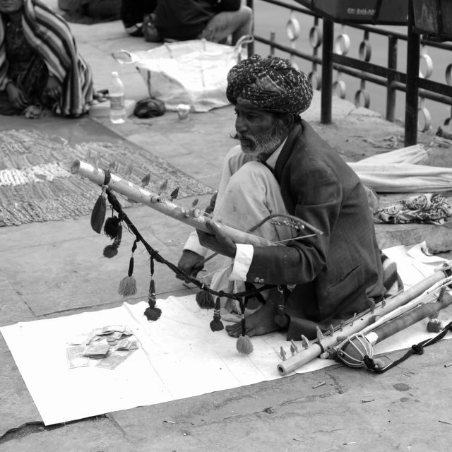 Old man playing traditional Indian musical instrument